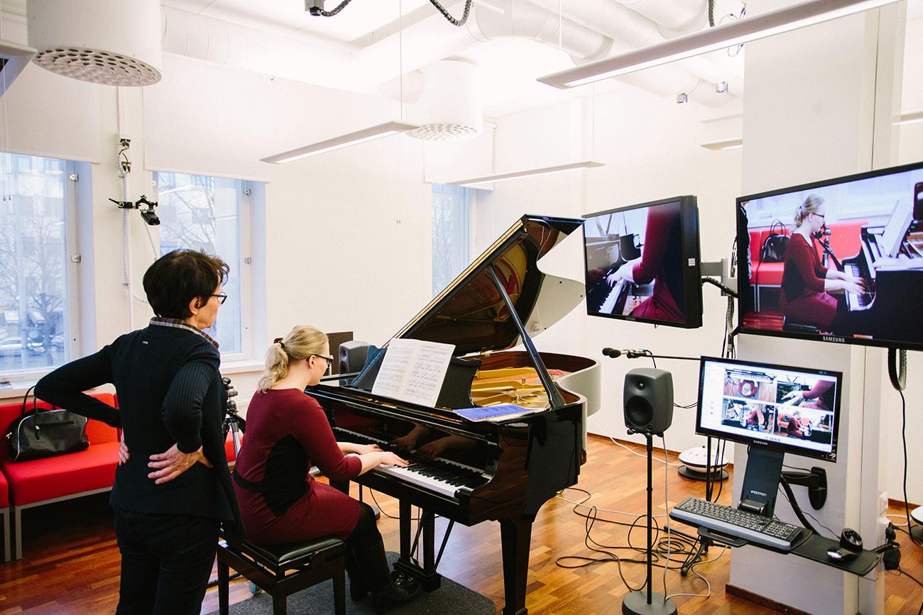 Marja-Leena Mikkola soittaa Griegiä pianolaboratoriossa. Kristiina Kask-Valve tarkkailee Mikkolan asentoa ja käsiä myös kuvaruudulta, jolloin virheasentoihin on helpompi puuttua.