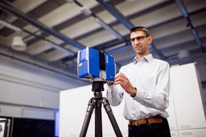 Kalle Tammi esittelee laserkeilauksessa käytettävää 3D-skanneria, joka luo parissa minuutissa ympäristöstä kolmiulotteisen kuvan, joka sisältää kohteen mittatiedot.